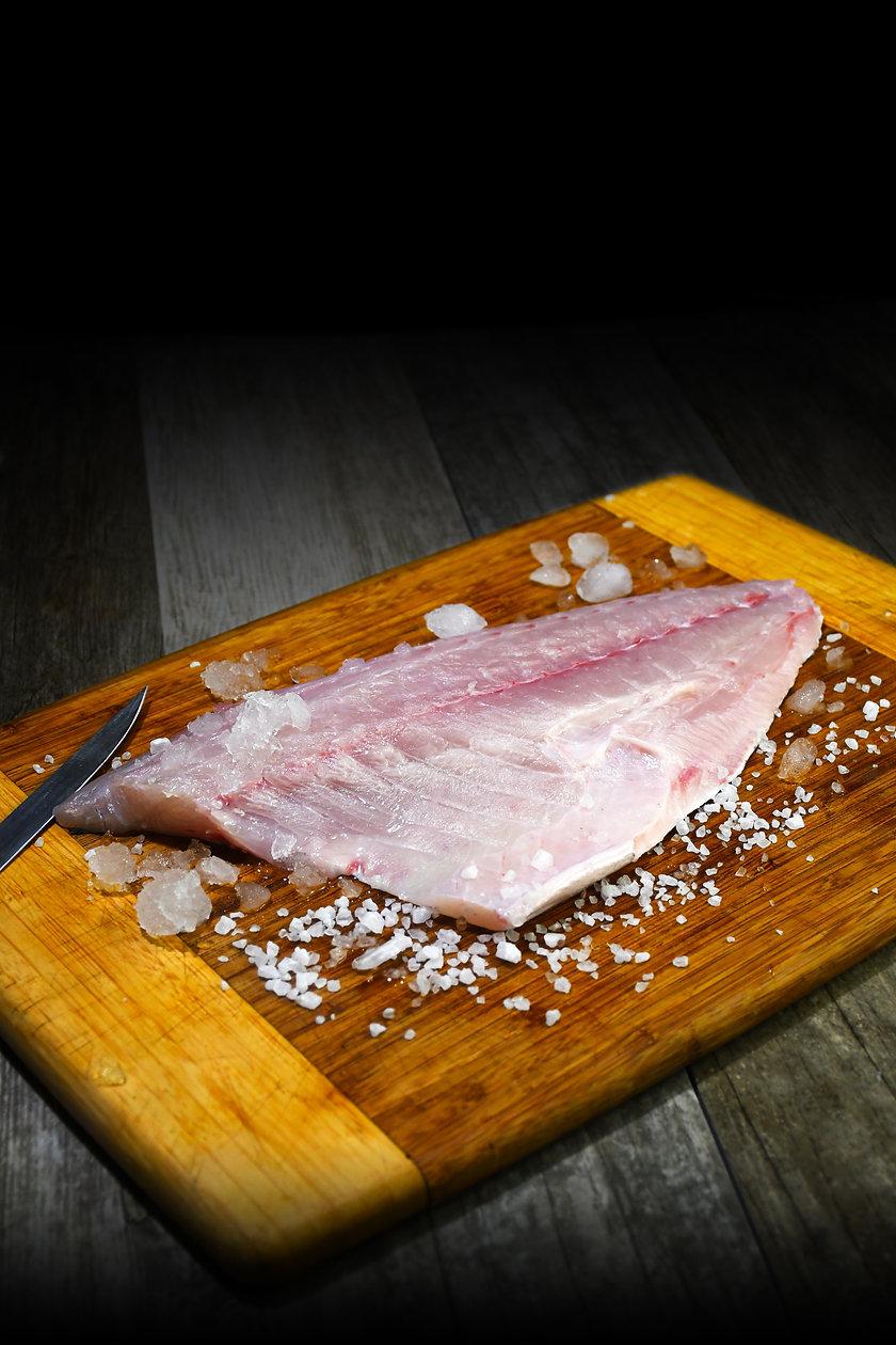 Baja Kanpachi (also known as Kampachi, Amberjack, or Longfin Yellowtail) fillet on cutting board with knife