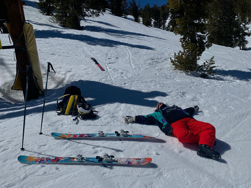 skier relaxing on the slope next to equipment