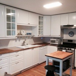 wood countertop and glass door white kitchen traditional.jpg