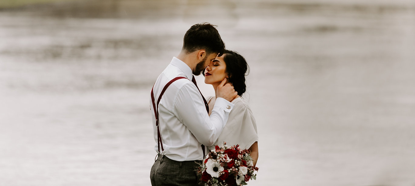 Bride kissing groom in front of River Thames with red and white bridal flowers