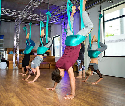 a group of people are practicing an inversion to decompress  spine on aerial yoga class
