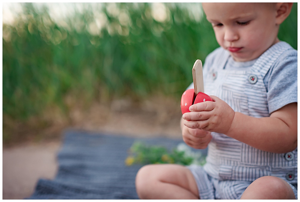 Toddler cutting wooden fruit