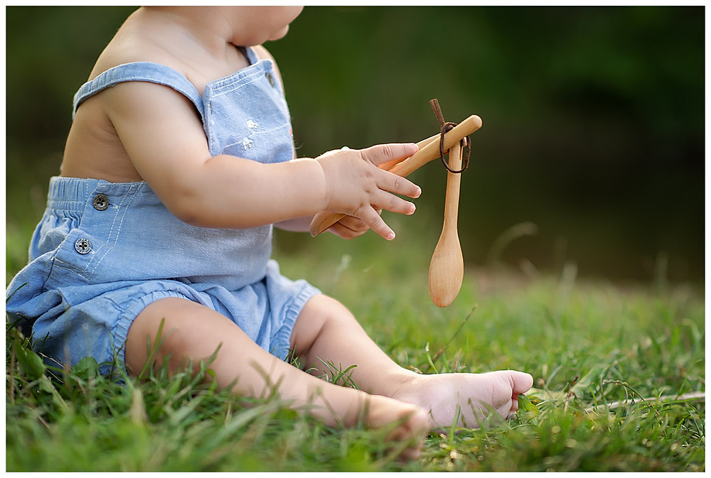 Baby playing with toy spoons