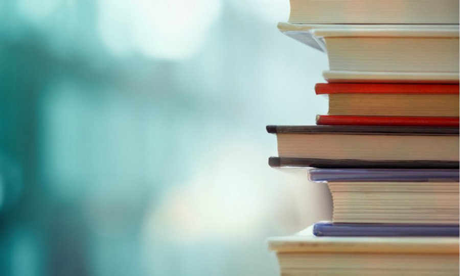 stack-of-books-against-blue-background.j
