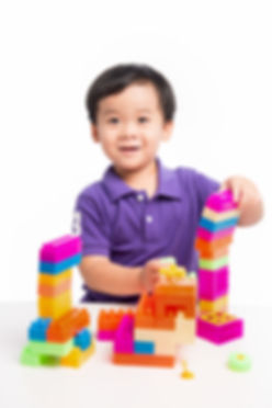 Kid boy playing with blocks from toy con