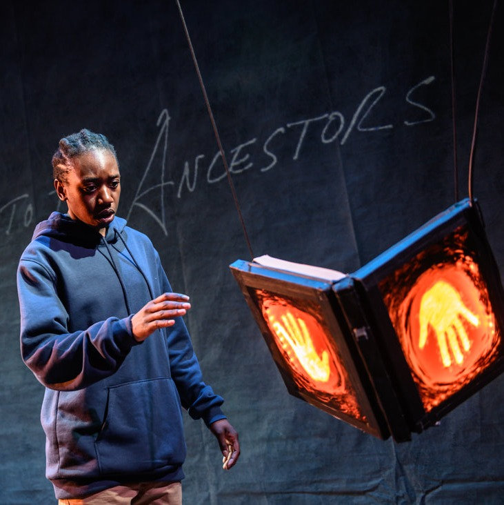 A Black teenage boy in a hoodie fearfully approaches a floating book with glowing hands on it. Behind him are the words Your Journey to the Ancestors.