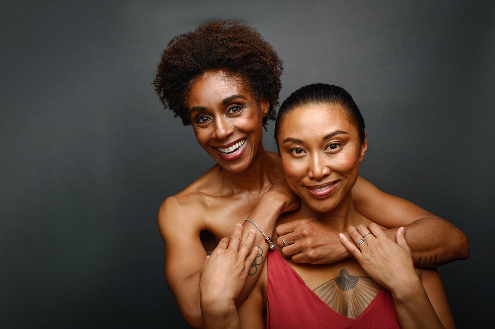 A Brown woman and a Black woman embrace and look at the camera, smiling.