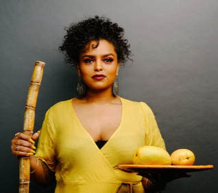 A Black woman looks at the camera holding sugar cane in one hand and a plate of mangoes in the other.