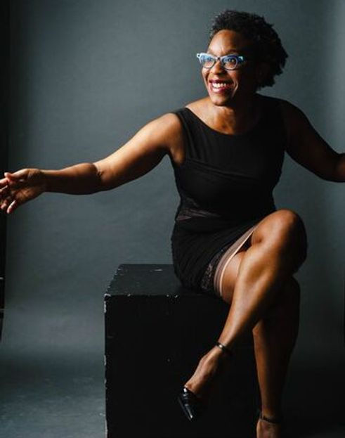 A Black woman with glasses sits on a stool smiling