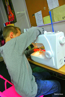 Bottle boy masters a sewing machine