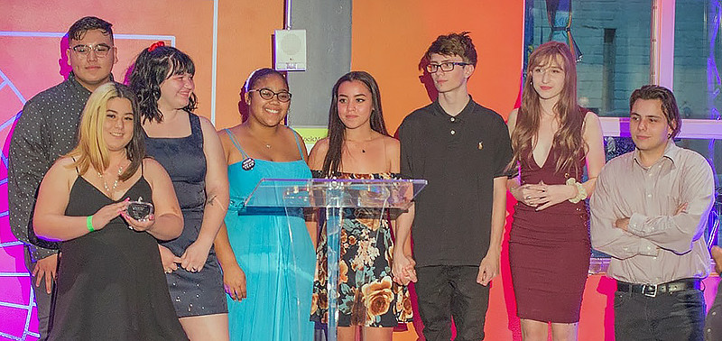 high school students dressed formally accepting award