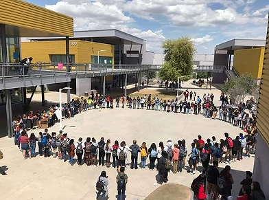 Large ring of students holding hand in solidarity for Day of Silence in the middle of a high school campus.