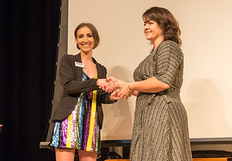 One person giving another person Sparkle GSA advisor of the year award.