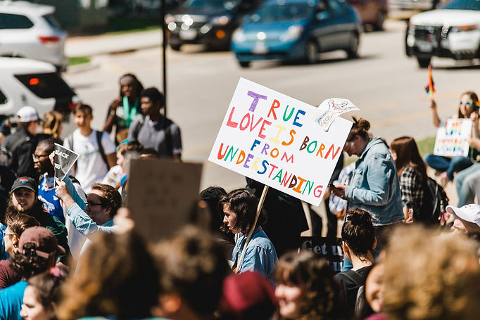"""Protest marchers carrying signs, most prominent sign is """"True love is born from understanding."""""""