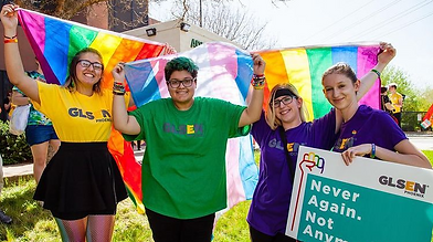 "Four students weating colored GLSEN shirts and holding pride flags and ""never again. not anymore."" sign"