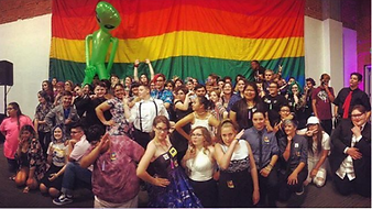 2019 Breaking the Silence Dance large group photo of students in front of large pride flag and blow-up alien.