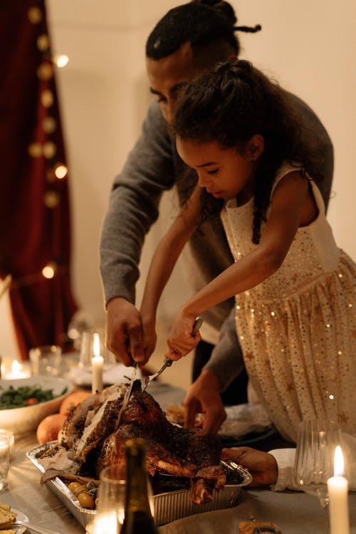 Father and daughter carving a turkey