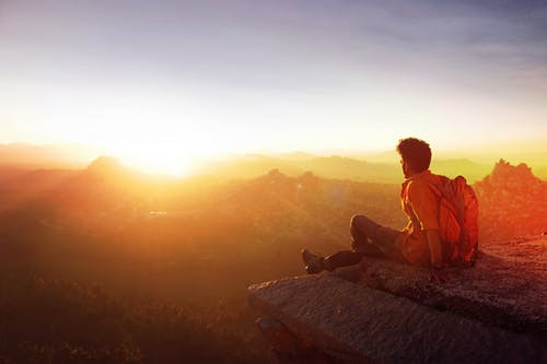 Hiker enjoying sunset over the next mountain ridge