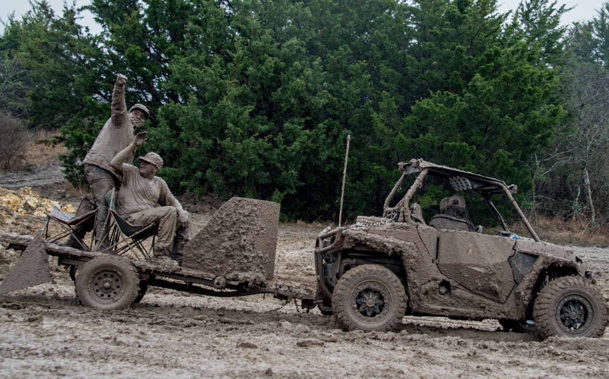 Very muddy men drive ATV