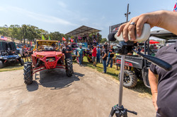 People surrounding red offroad truck