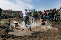 Men running in a mud pit