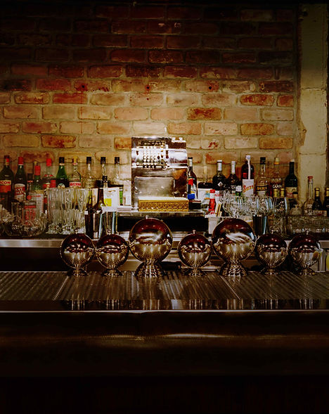The Varnish back bar with white brick, btls, and silver bar equipment.