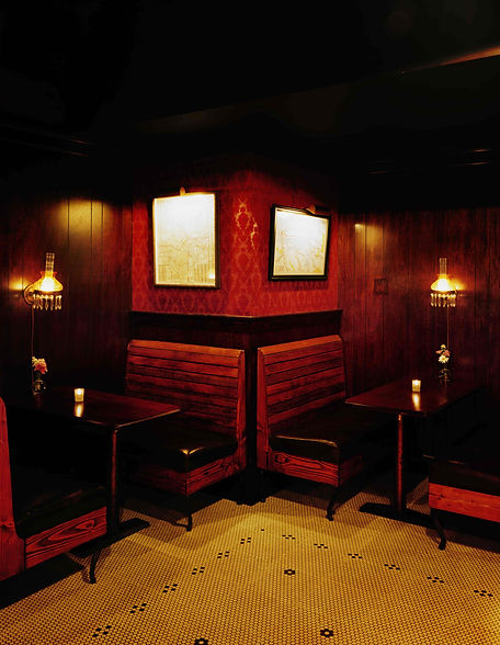 Wood boths with red patterned wallpaper in the glow of a lamp at the Varnish
