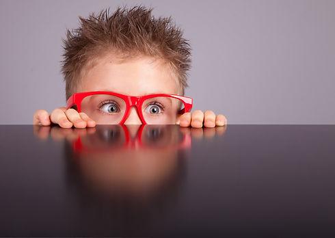 Five years old little cute boy hiding behind a table_edited.jpg