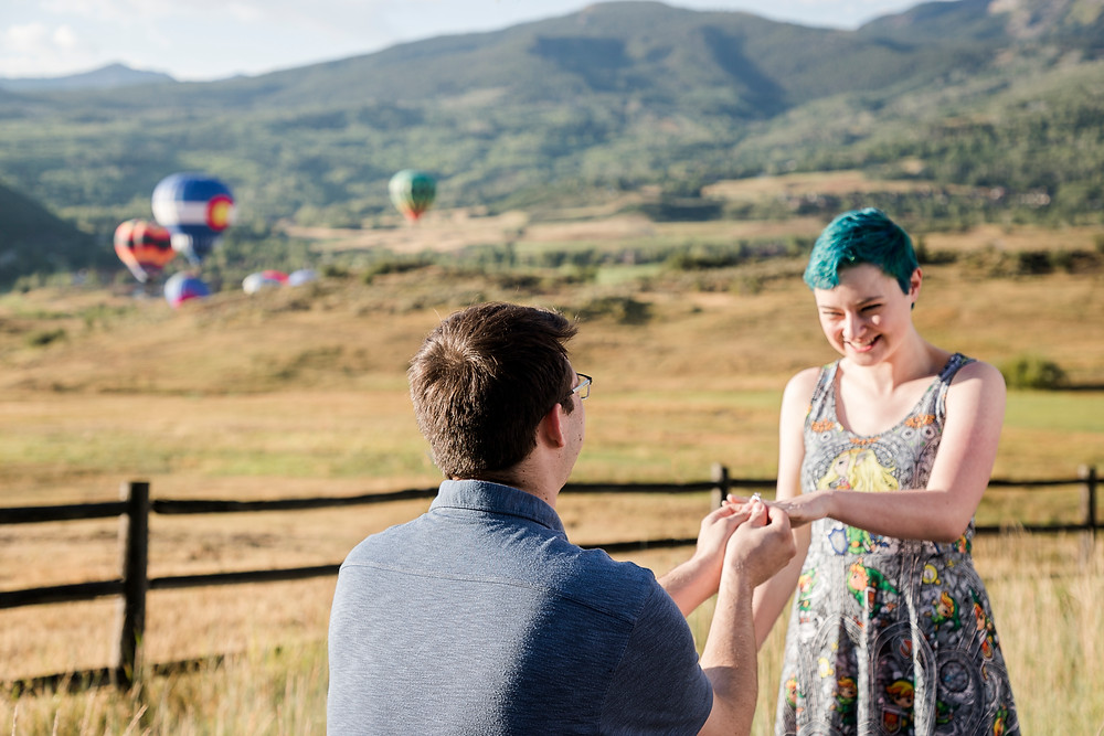 A man proposes to a woman in front of a field with hot air balloons in the background