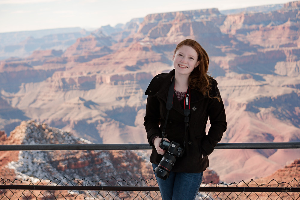 Woman holding a camera stands in front of the Grand Canyon smiling