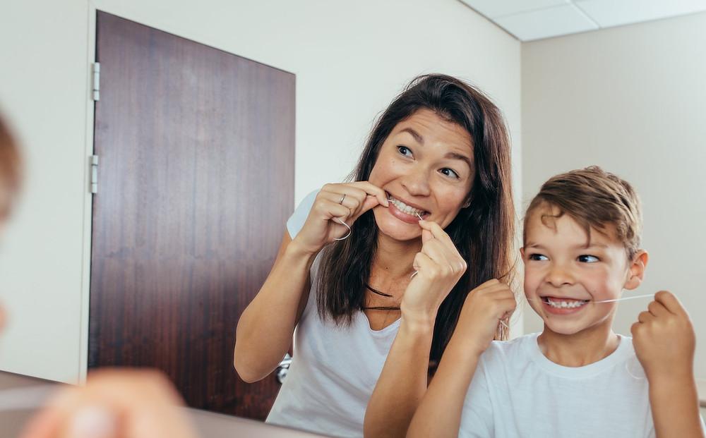 Mutter und Kind verwenden Zahnseide vor dem Spiegel