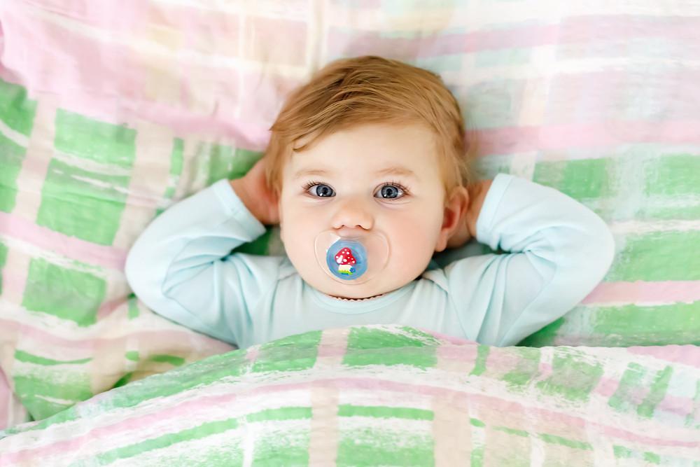 Kleinkind im Bett mit Schnuller