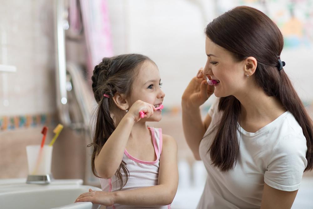Mutter und Tochter beim Zähneputzen im Badezimmer
