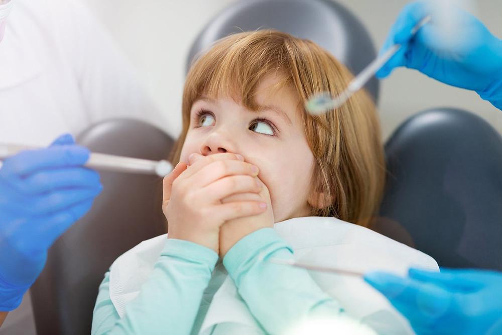 Kind versteckt seine Zähne vor dem Zahnarzt