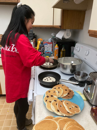 Editor, Anna Lowery, cooking pancakes for Pipes of Pancakes!