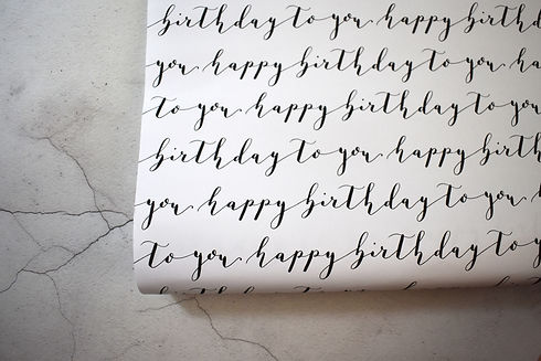 happy birthday to you in black calligraphy on a white sheet of wrapping paper on a marble background