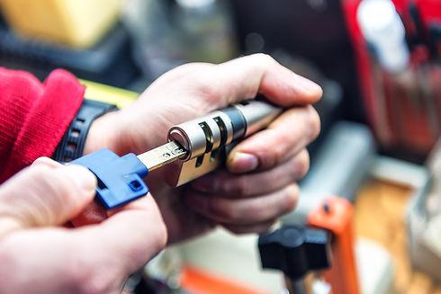 locksmith is testing door lock cylinder