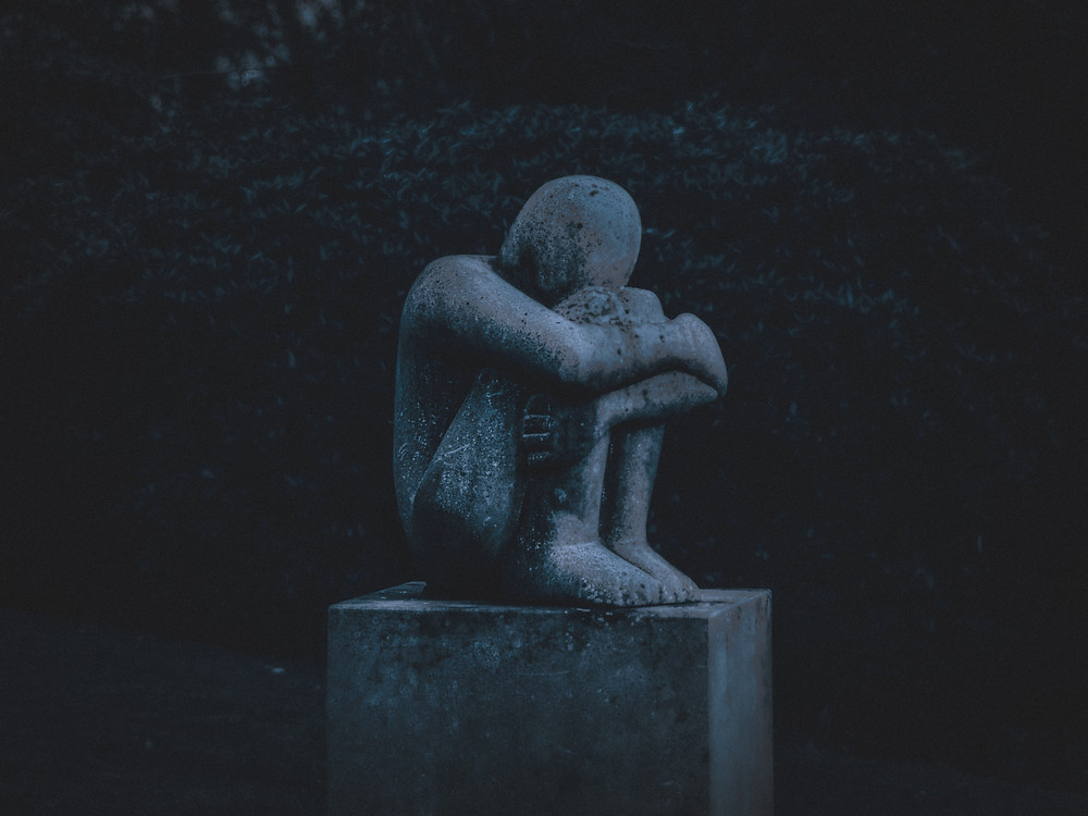 A statue of a person experiencing loss, trauma and grief