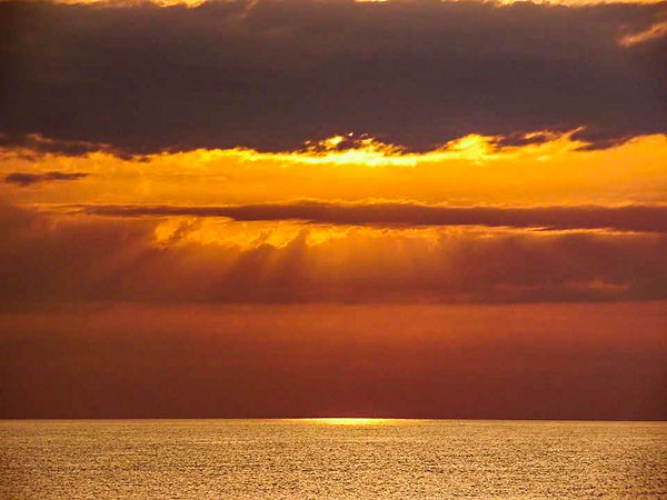 sun beind the clouds and sunrays over the ocean in Panama City Beach Florida