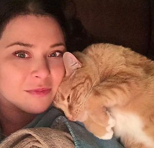 Woman snuggling with orange foster cat