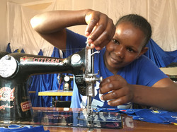 Young girl learning to sew