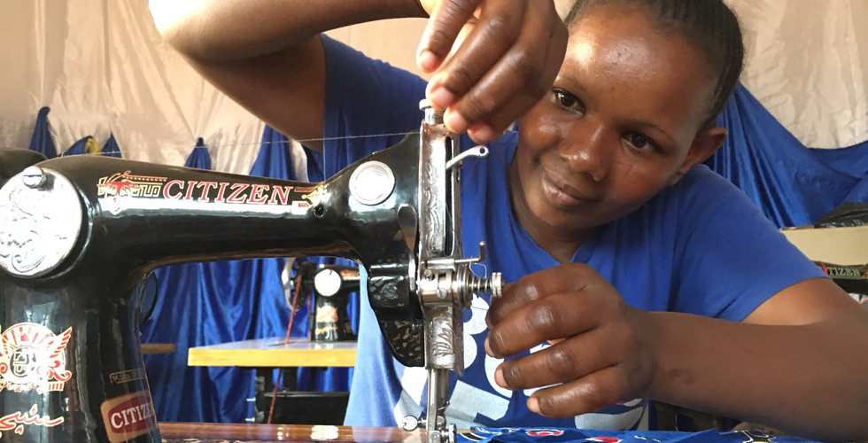 Young women trained by KiliTech learn to sew