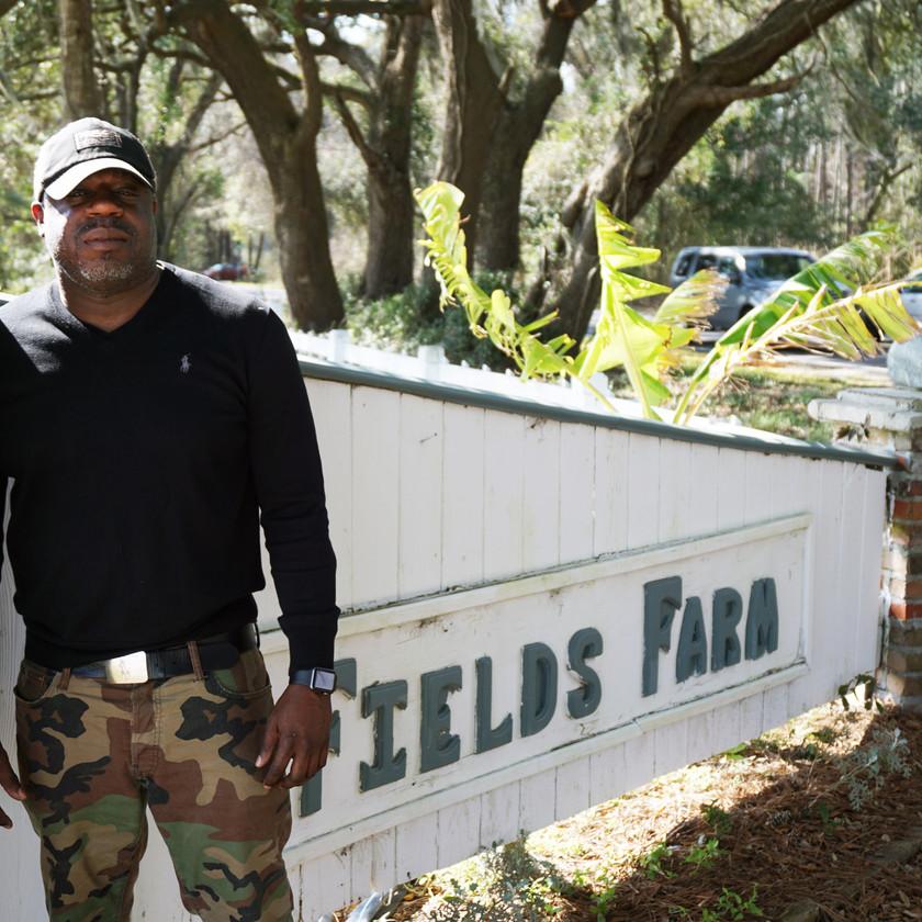 Mr. Devonne Hammond in front of the Fields Farm sign
