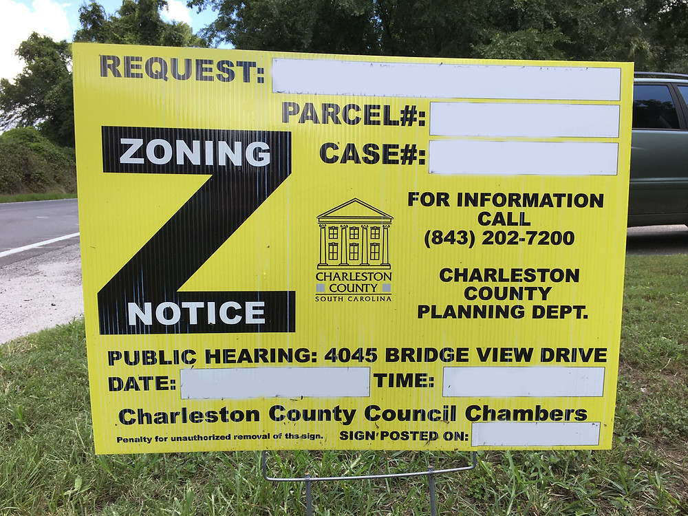 A yellow Charleston County zoning notice sign is staked in the grass