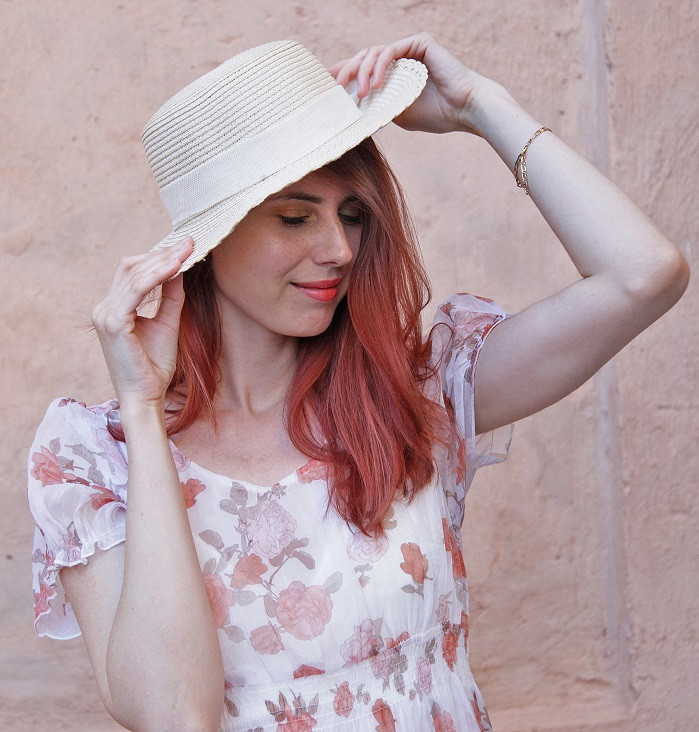 Red hair actress wearing a white dress with folowers holding the hat on her head while having a dreamy expression