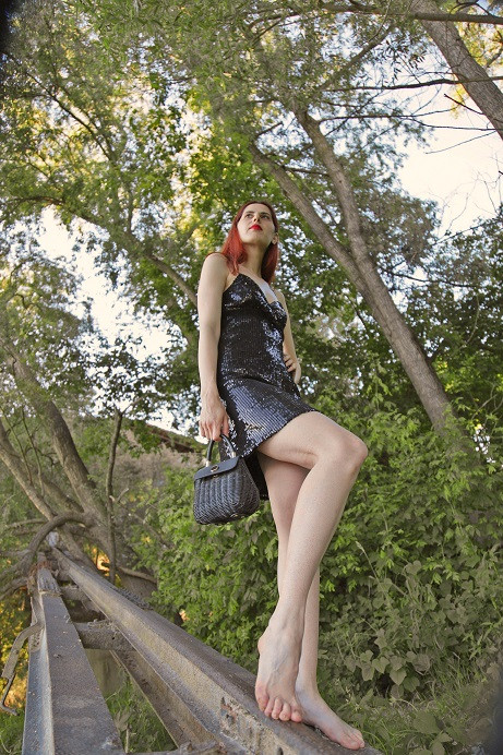 Model in an urban elegant little shiny black dress with a bag posing barefoot on some railways in the nature