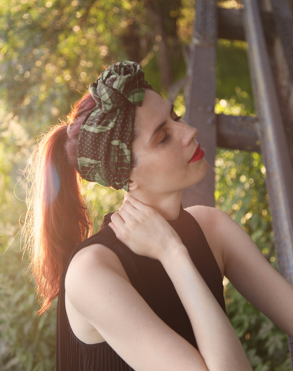 Model posing with sun shines reflected on her red hair having a dreamy expression with eyes closed and hair accesorise posing in the nature