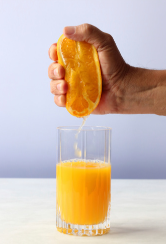 Image of a man squeezing an orange with the juice funneling into a tall juice class. Iconography for SEO juice.