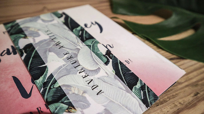 wedding stationery invitation with watercolour design and tropical leaf wrap band
