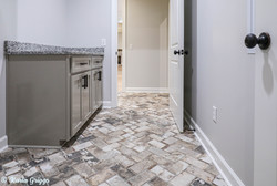 Herringbone pavers and custom cabinets in laundry area